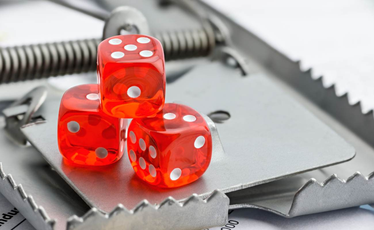 3 red dice on a mousetrap demonstrating the concept of gambling risk/scams.