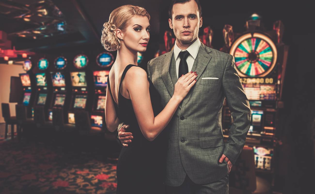 Well dressed man and woman in a casino, by the slot machines