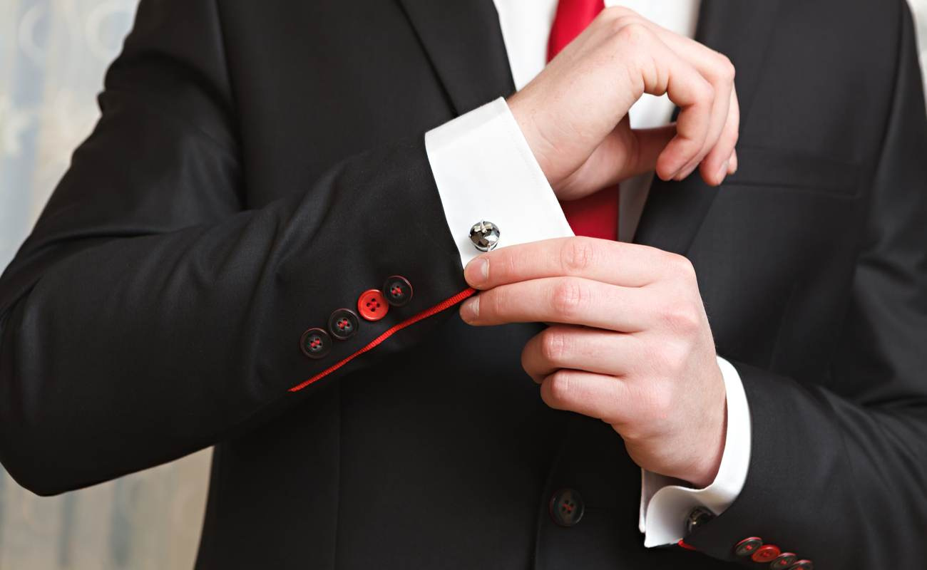 Man clasps cufflink on his shirt, wearing a black blazer and red tie.