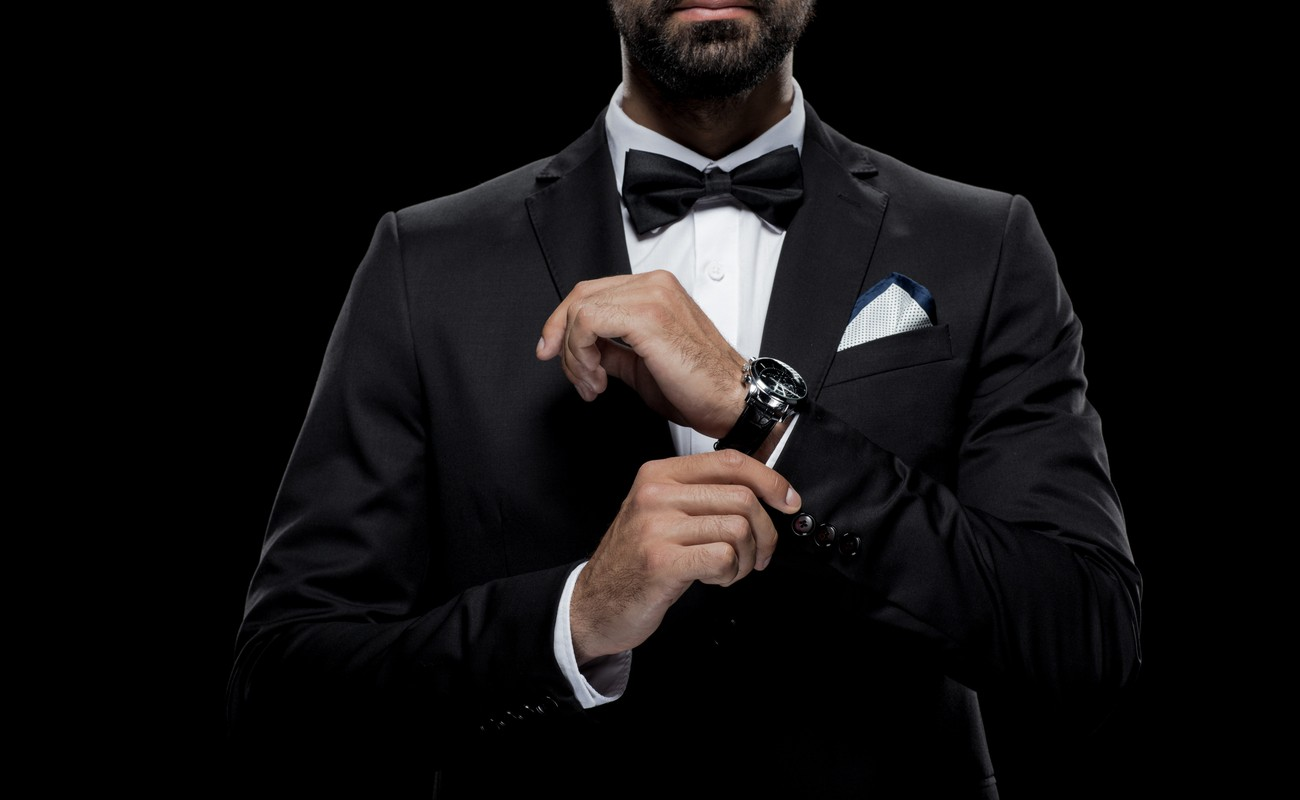Man in a tuxedo with a bow tie and wristwatch, with a black background.