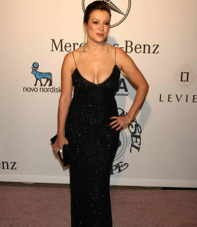 Jennifer Tilly wearing a low cut black evening dress.