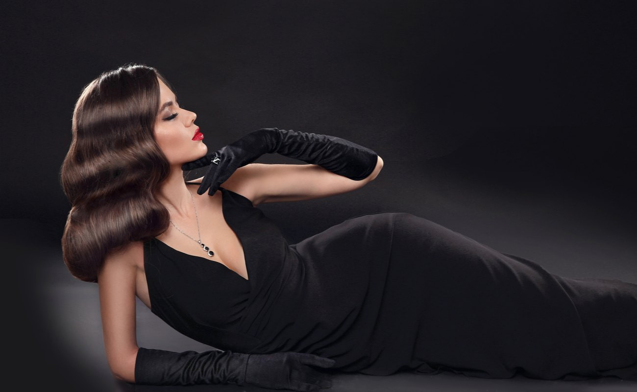 Elegant lady wearing a black floor-length evening gown and long black gloves