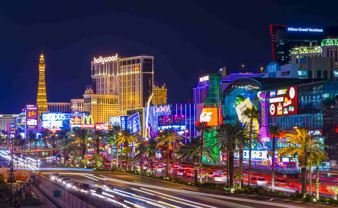 The Strip in Las Vegas, Nevada, at night with bright lights and palm trees.