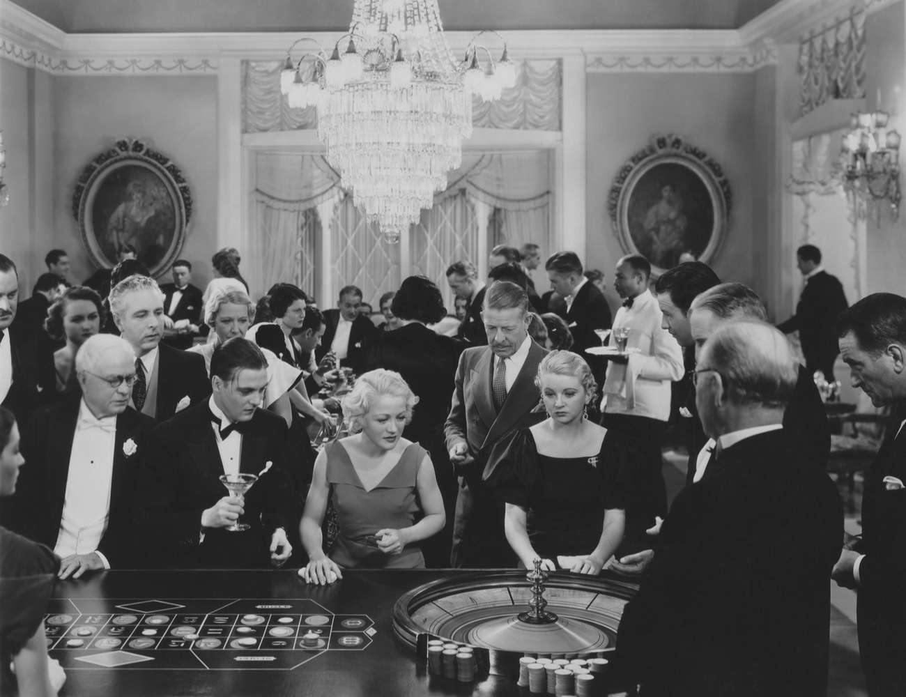 Black and white casino scene with people gathered around roulette wheel