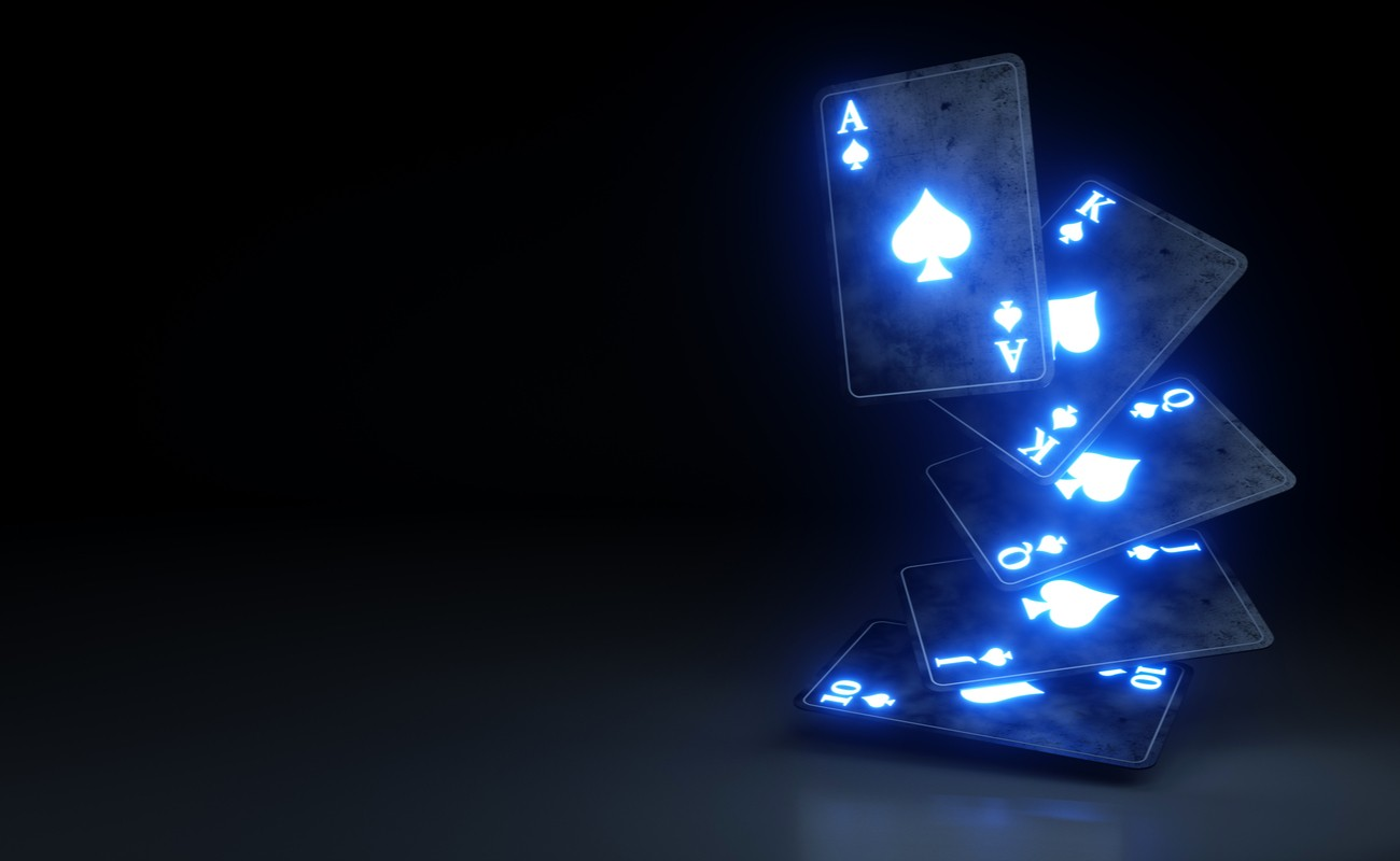 Light up blue playing cards mid air with a black background.