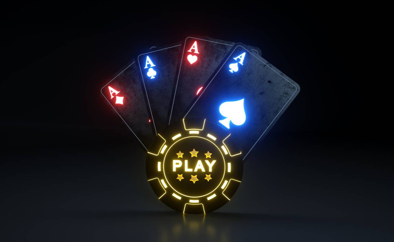 Lit up ace cards behind a lit up poker chip with a black background.