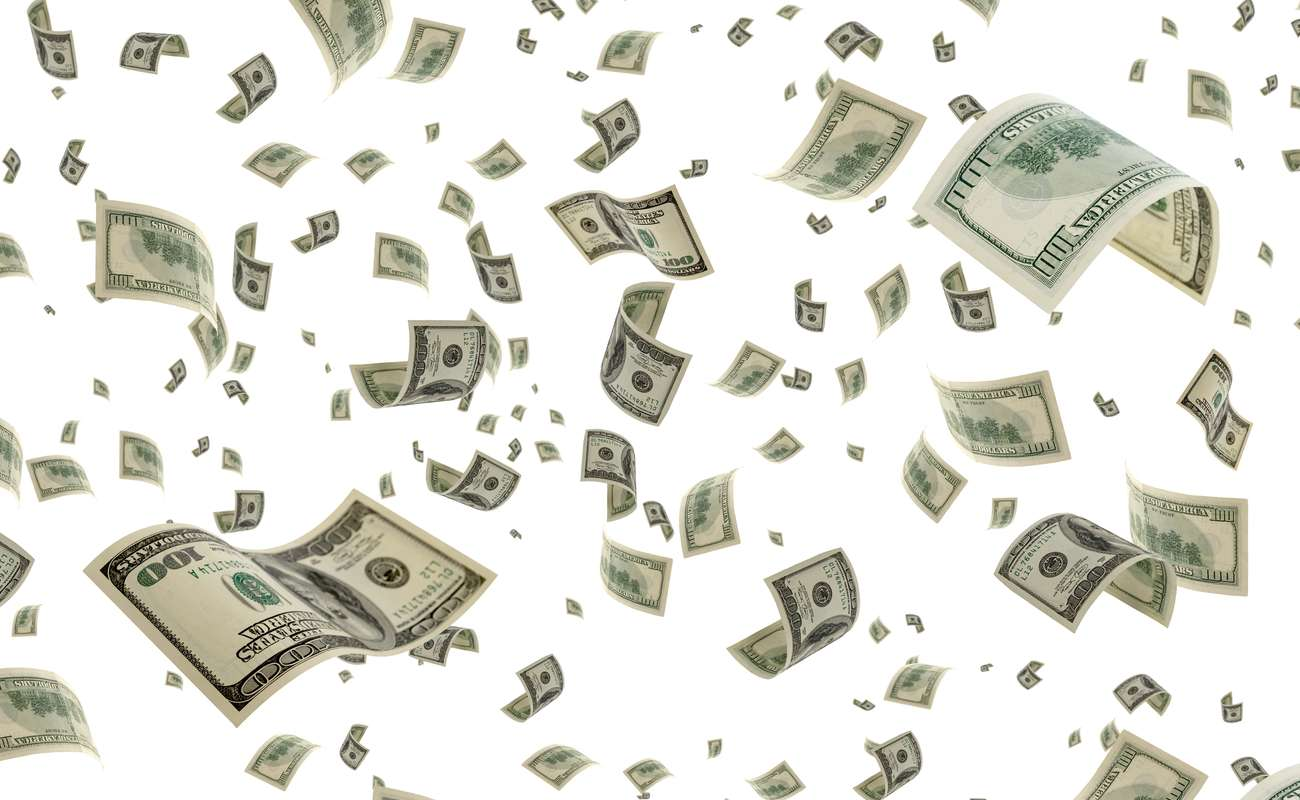 Lots of 100 dollar bills floating everywhere in front of a plain white background.