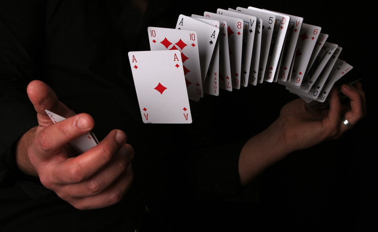 A pair of hands with cards spread across and floating in between them