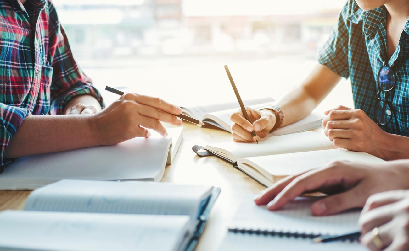 3 people studying with pencils and notepads on a wooden surface