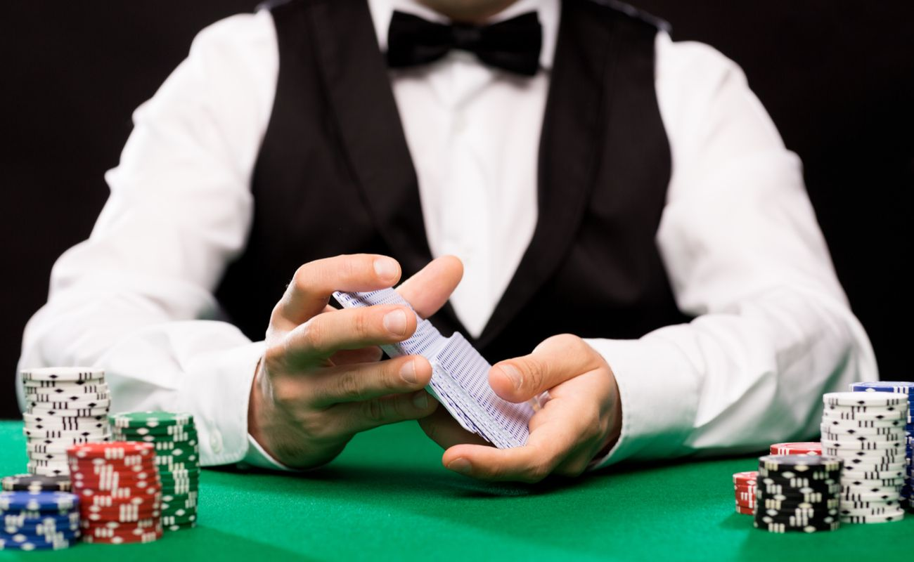 Man in smart clothes shuffling cards on a table with poker chips