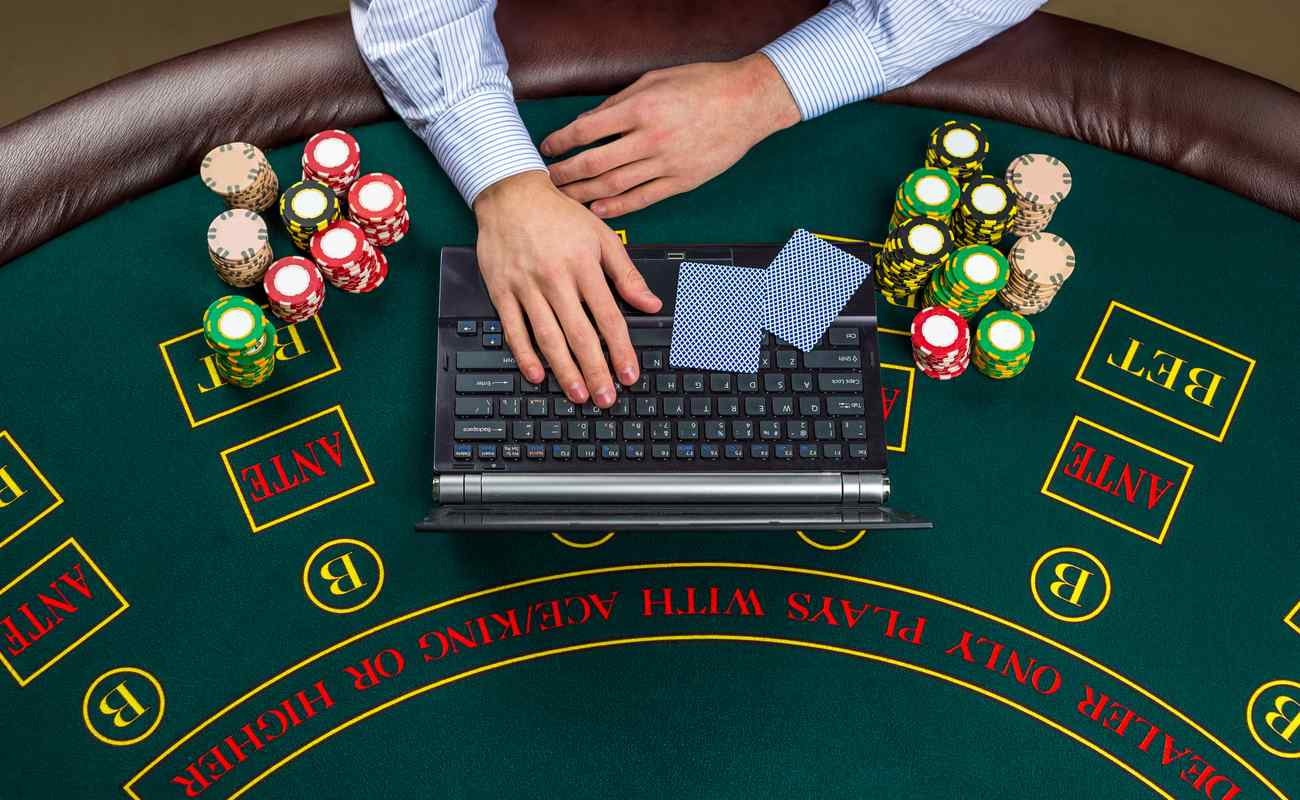 Someone on a laptop placed on a poker table