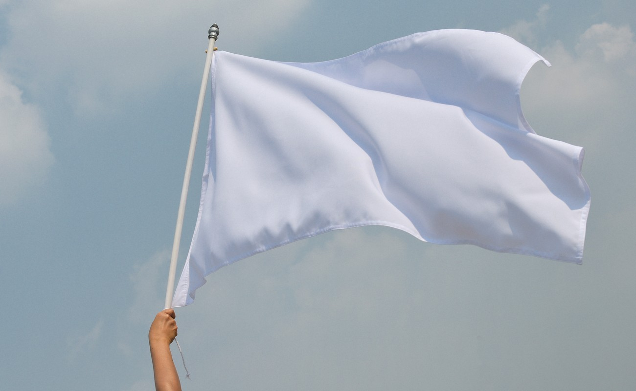 Someone holding a white flag in the air signaling surrender