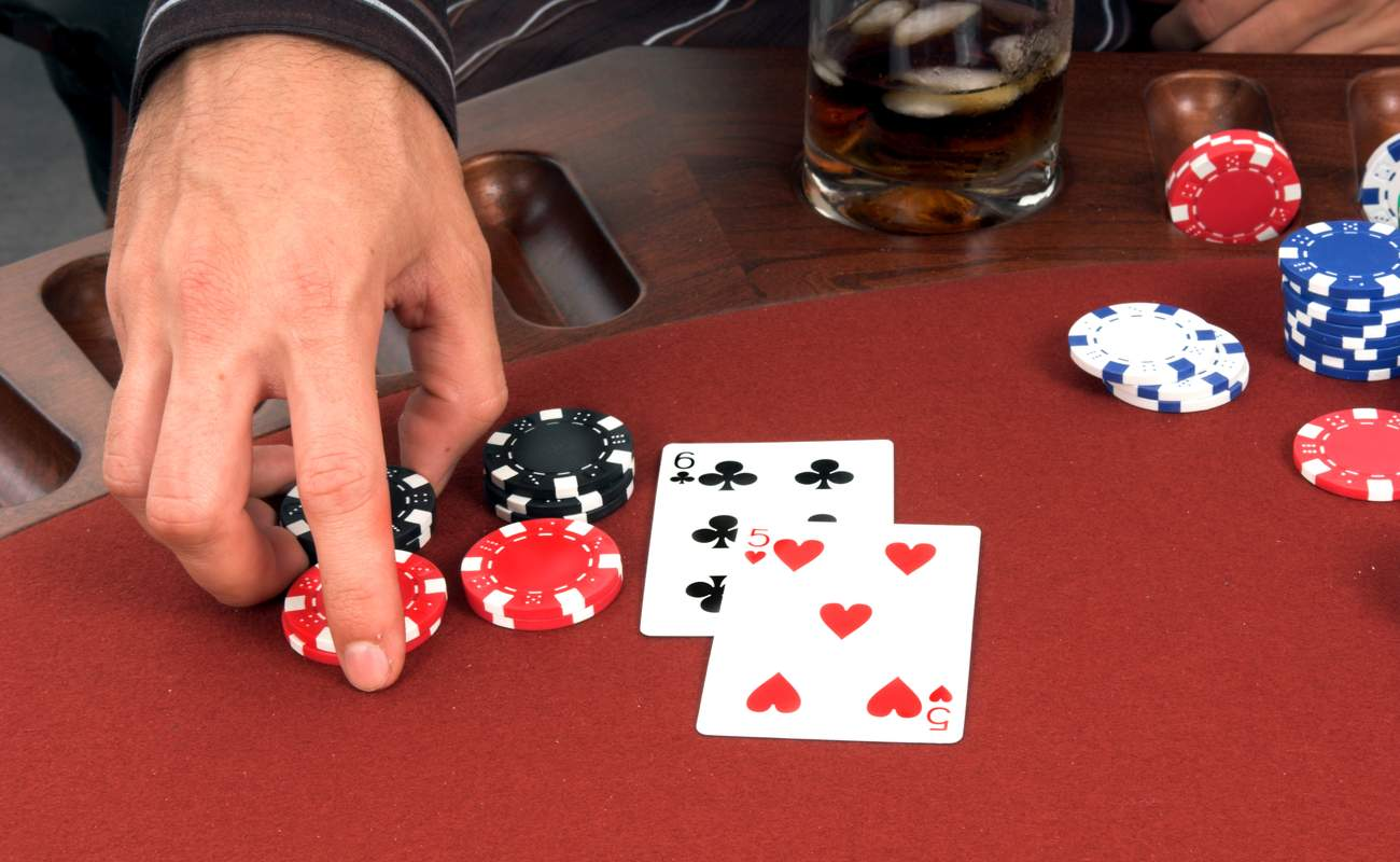 Someone's hand about to move their chips to double down in poker game