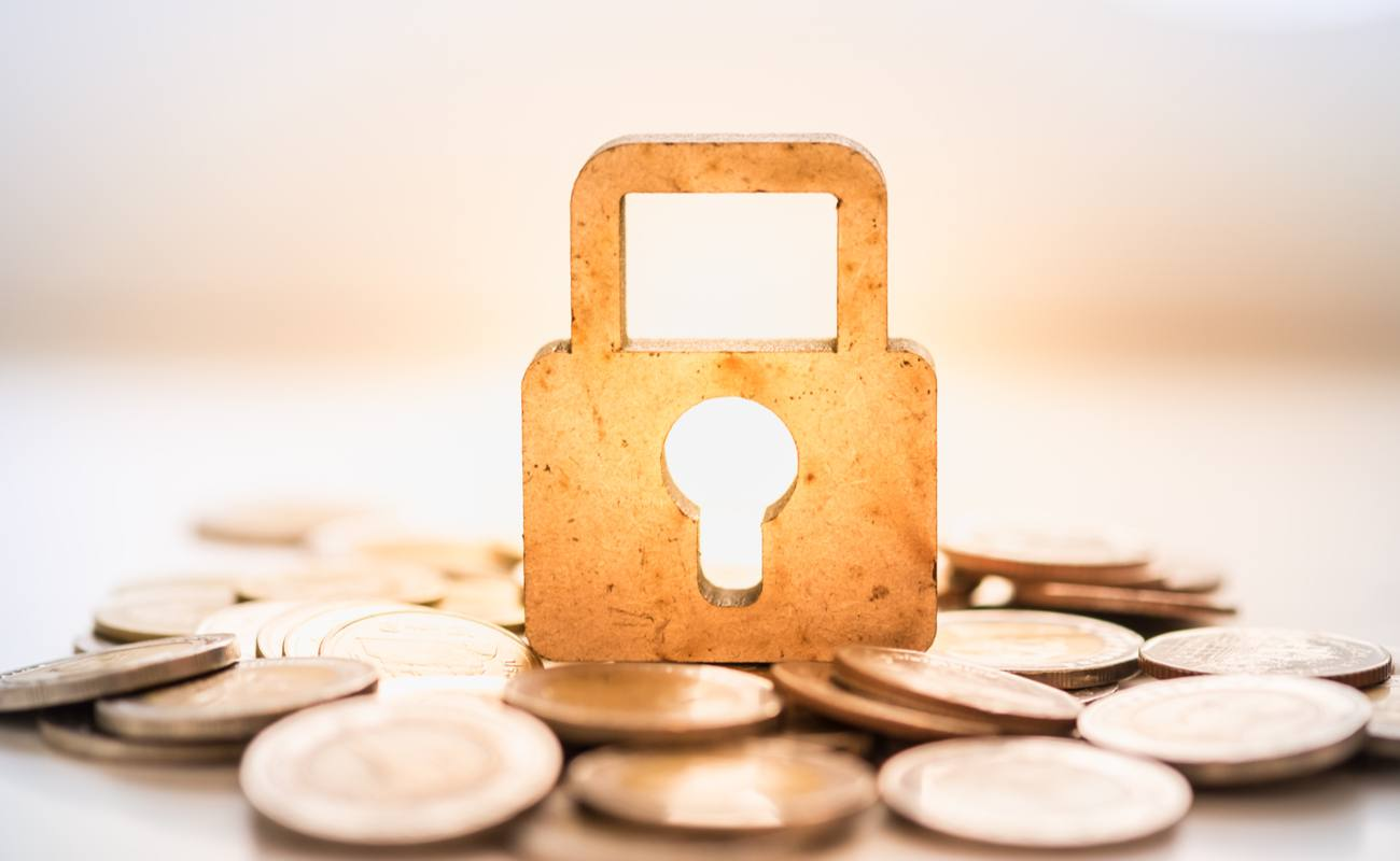 Gold padlock standing up on many scattered coins on a white table.