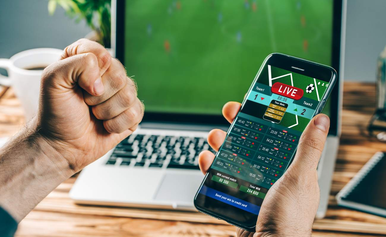 Man celebrating his win on a sports betting app with his phone in one hand