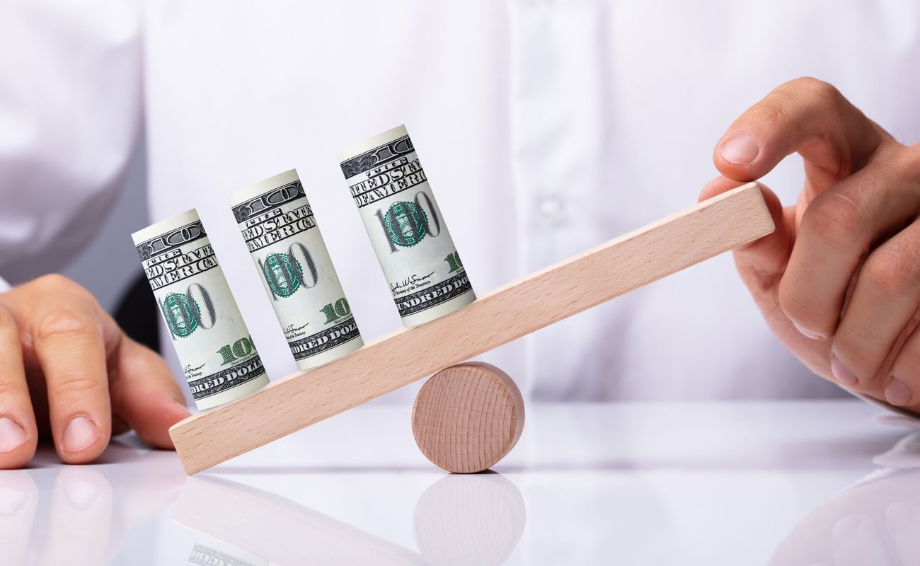 A person's hand balancing 3 rolled up dollar bills on a wooden seesaw.