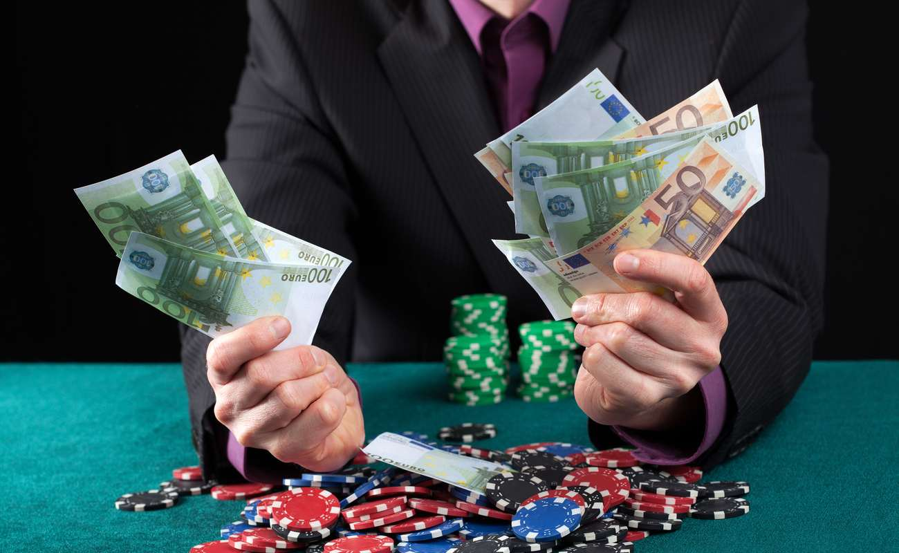 Man holding many euro notes in his hands with poker chips stacked up