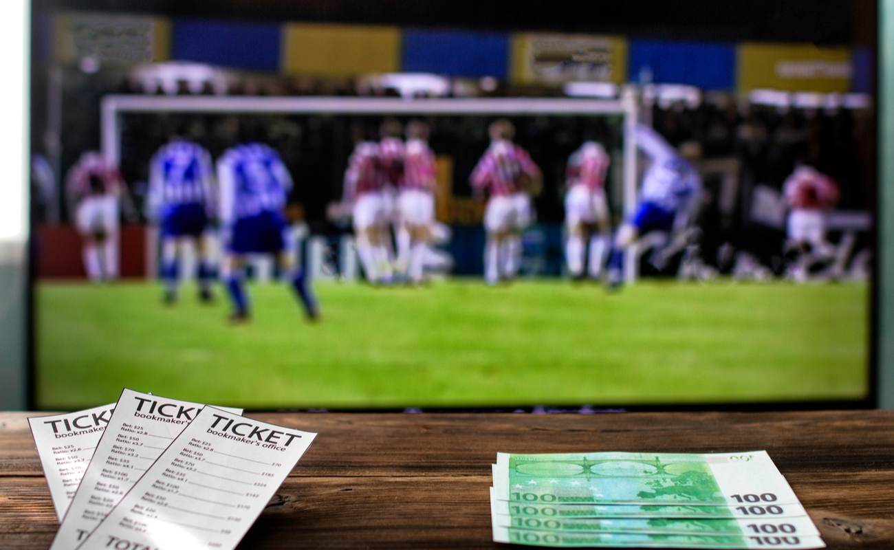 3 sports betting tickets next to four hundred dollar bills on a brown table in front of a blurred TV screen displaying football.