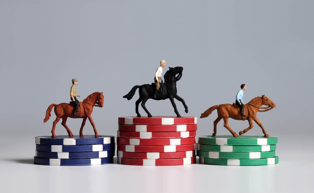 1 plastic toy brown horse and jockey on a stack of blue poker chips, 1 plastic toy black horse and jockey on a stack of red poker chips and 1 plastic toy brown horse and jockey on a stack of green poker chips