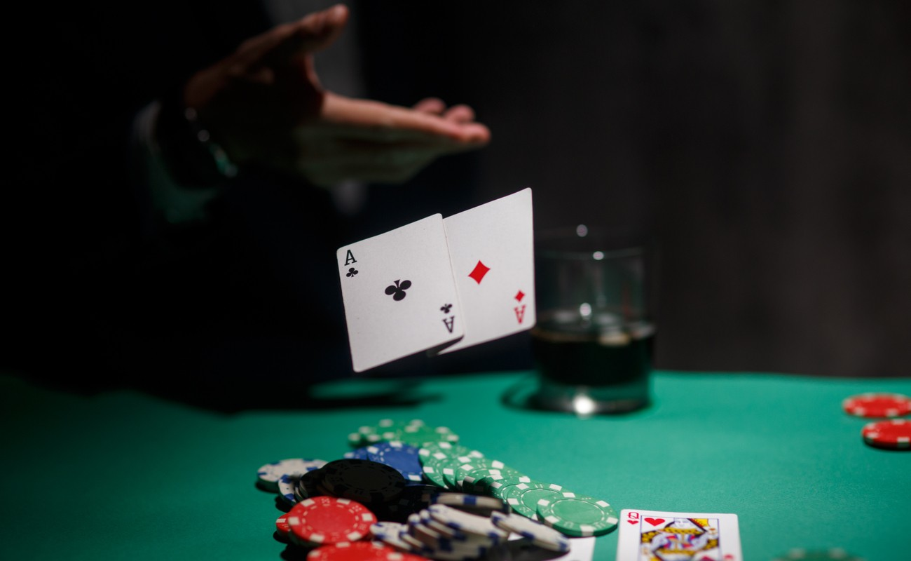 Someone throwing their cards on the poker table with poker chips