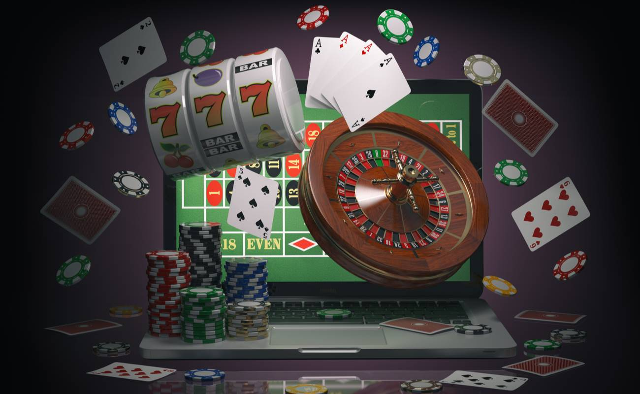 Poker chips, poker cards, spinning wheel and slot machine flying out and around a laptop.