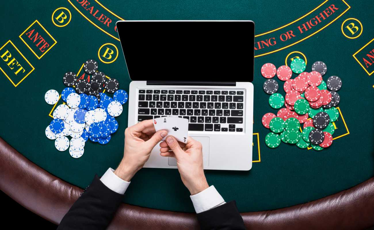 Hands holding 2 aces cards with a laptop on a poker table