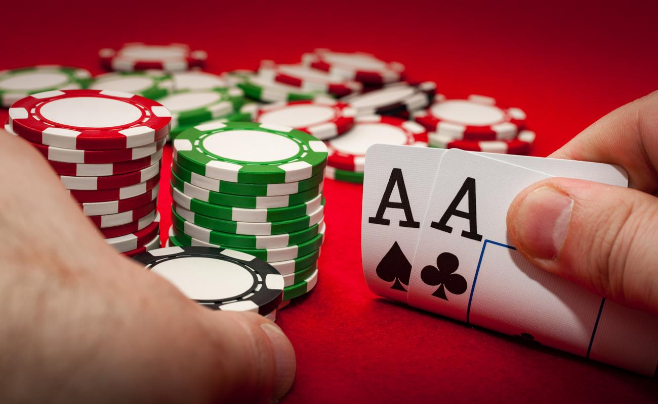 Hands holding 2 aces and poker chips on a red surface