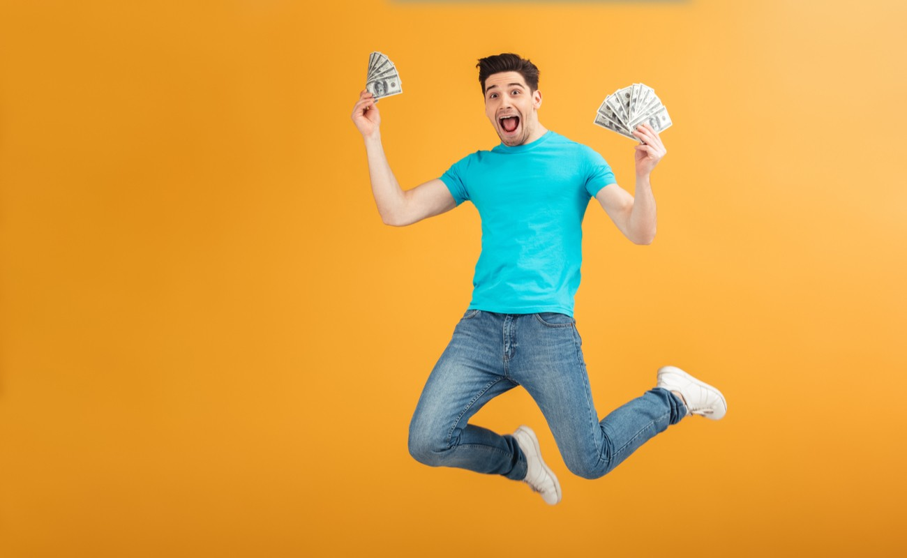 Man jumping holding money in both hands with orange background