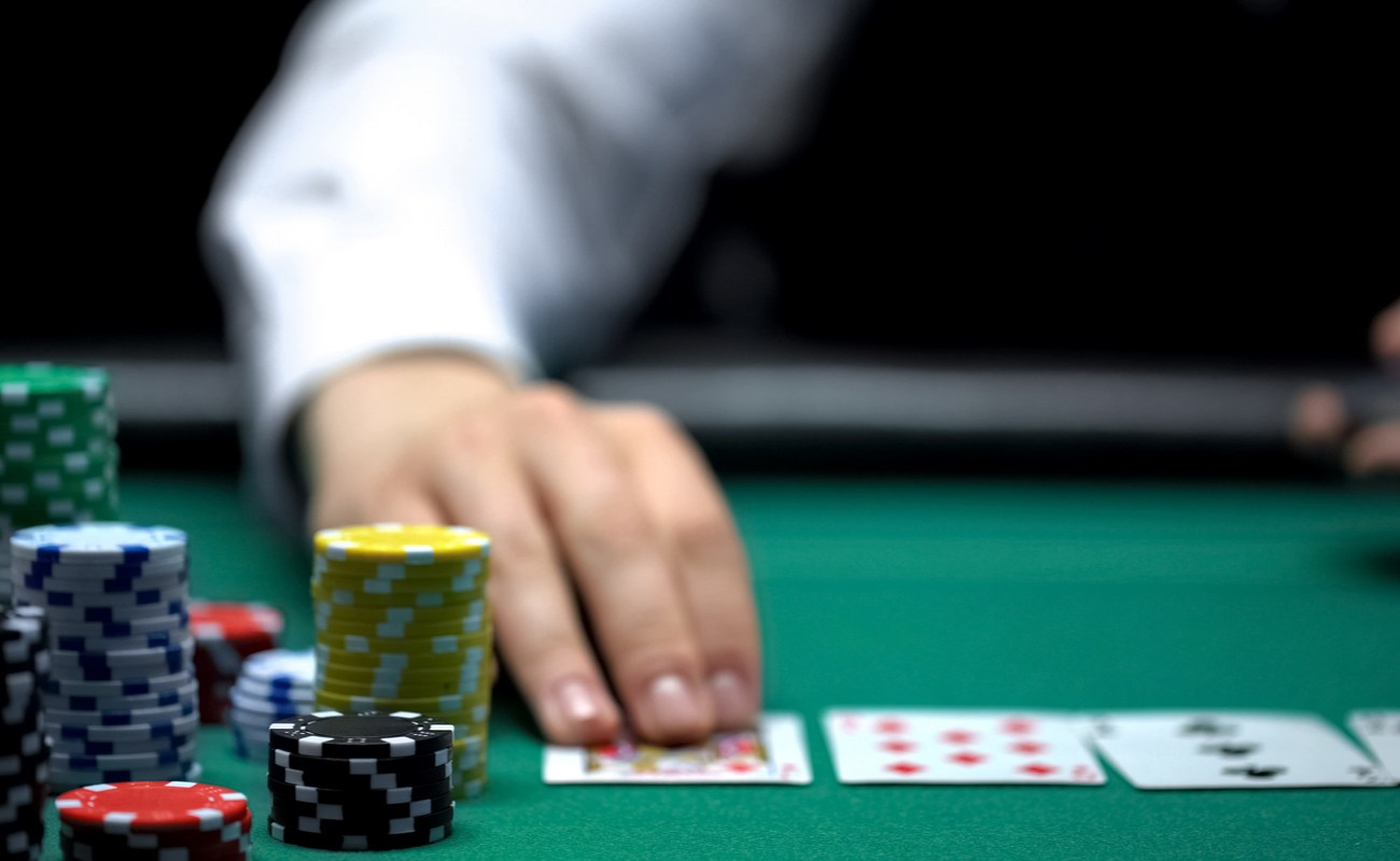 Close up of hands in between piles of poker chips on casino games table