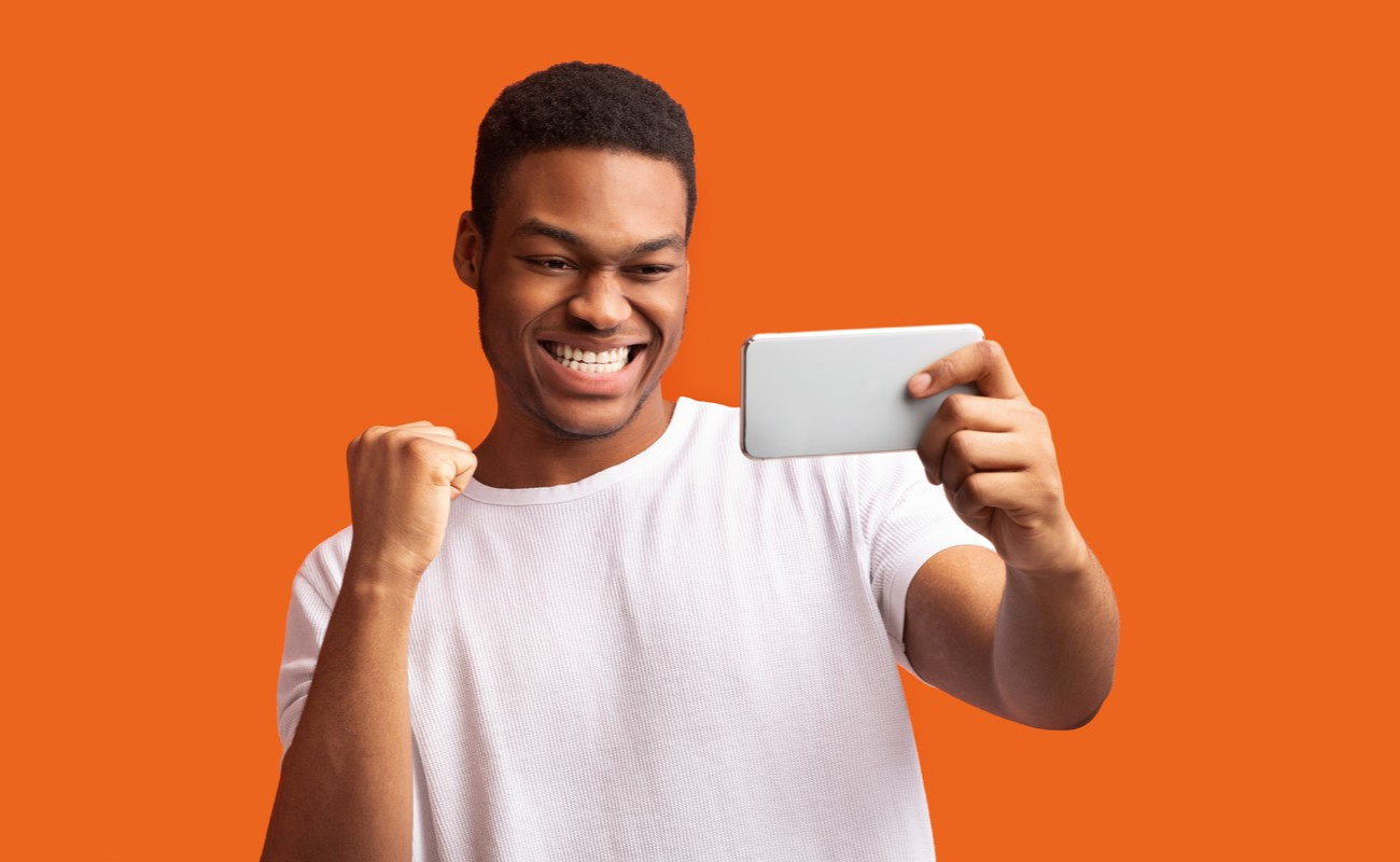 Man staring and smiling at mobile phone in front of orange background