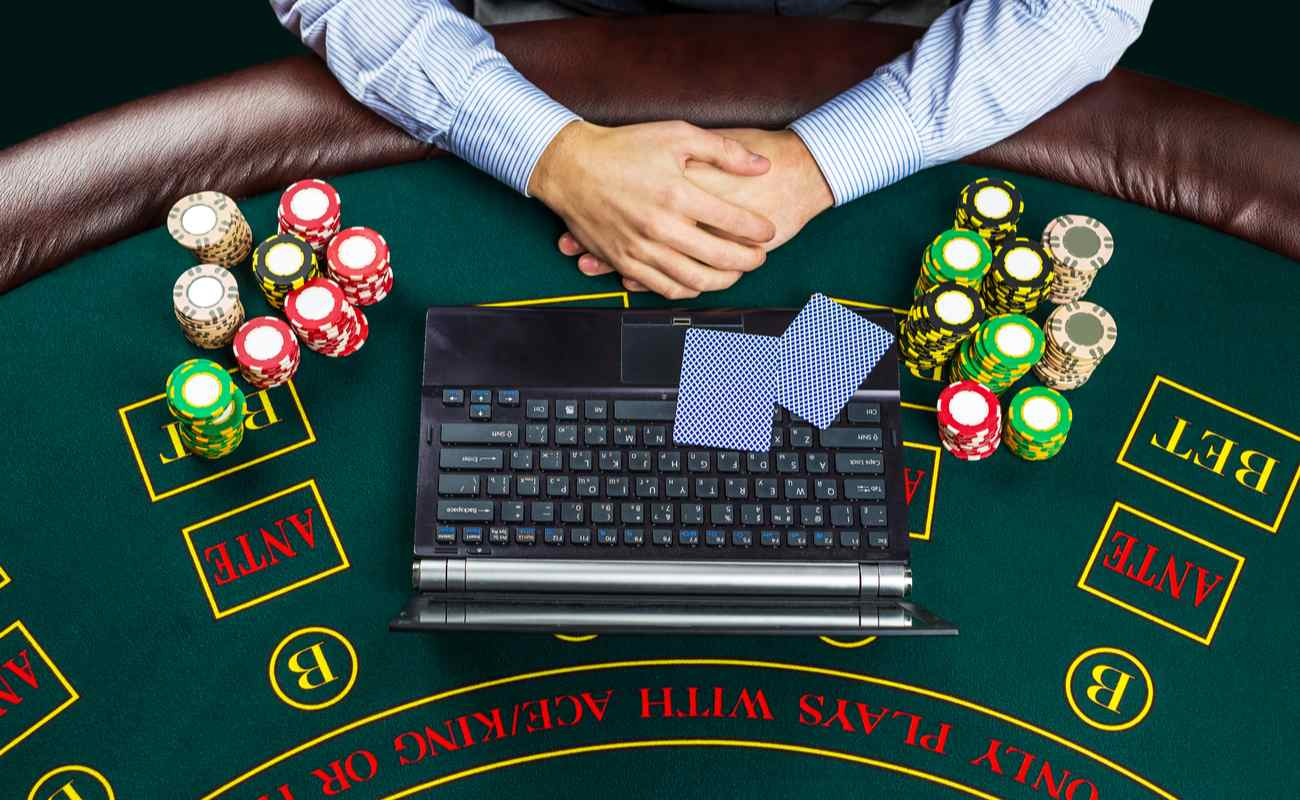 Closeup of poker player with playing cards, laptop, and chips