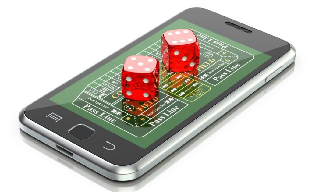 cellphone with online craps on screen and red dices, online gambling concept