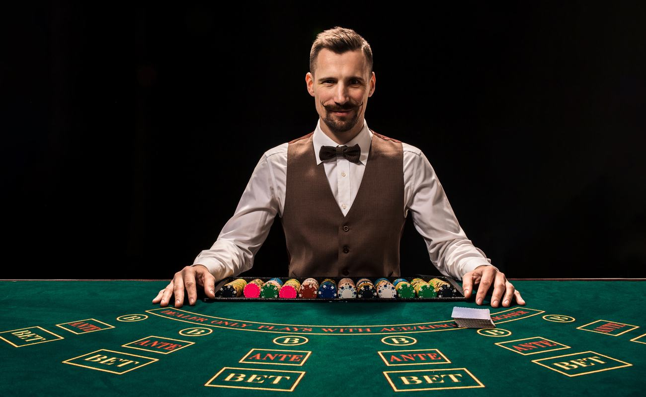 Portrait of a croupier holding playing cards, gambling chips on table