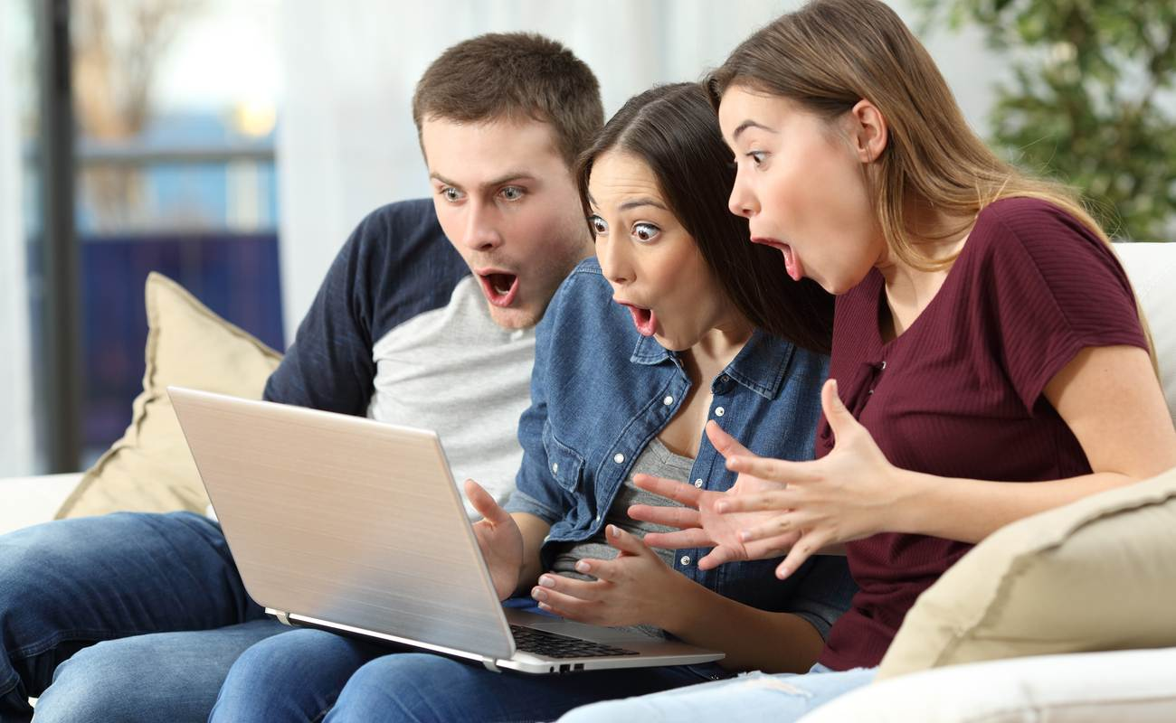 Three friends on computer on couch, amazed at online win