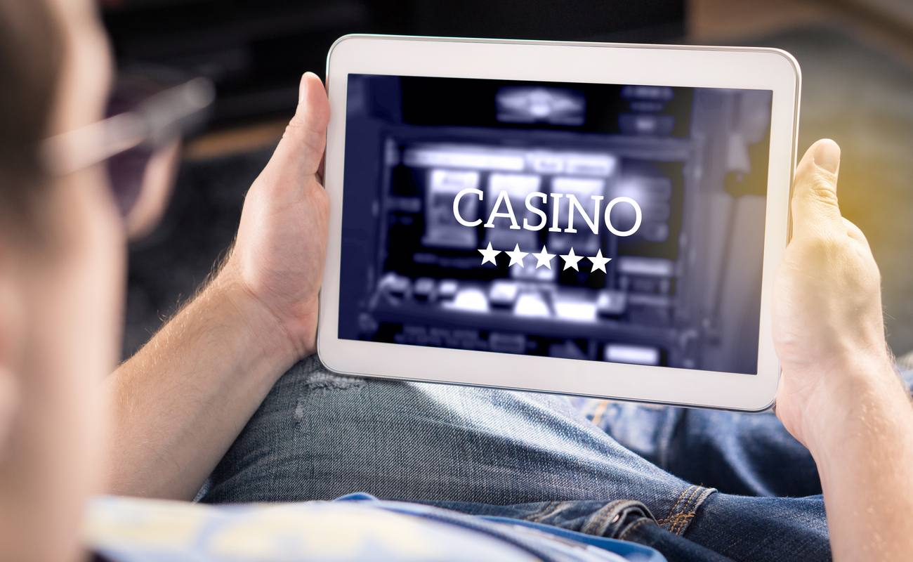 Man playing in an online casino with a tablet.