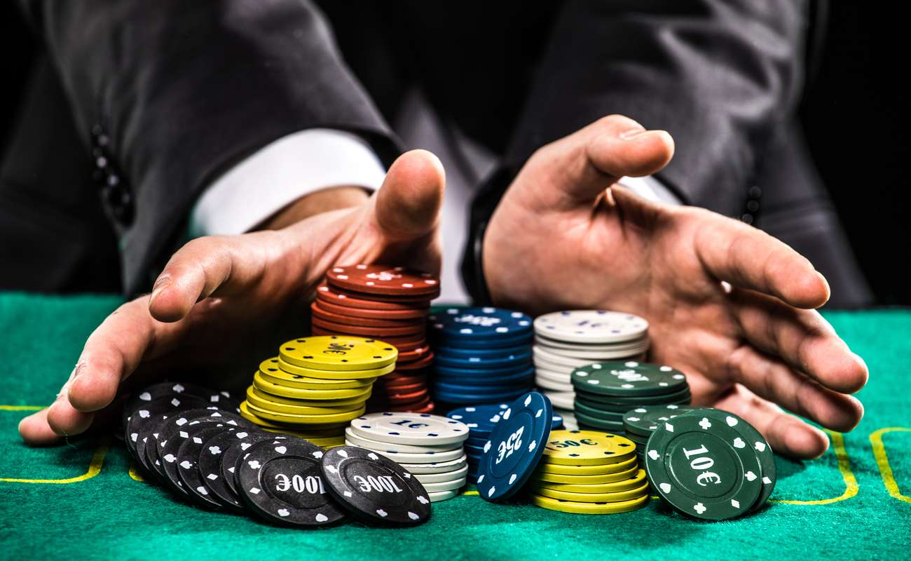 close up of poker player with chips at a green casino table