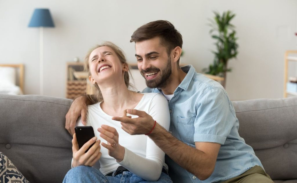 couple sitting together on the couch laughing about funny online joke holding a phone