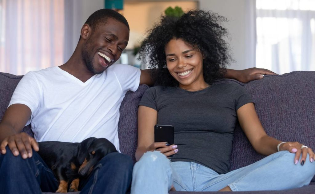 Happy young couple sitting on the couch playing online casino games on a cellphone