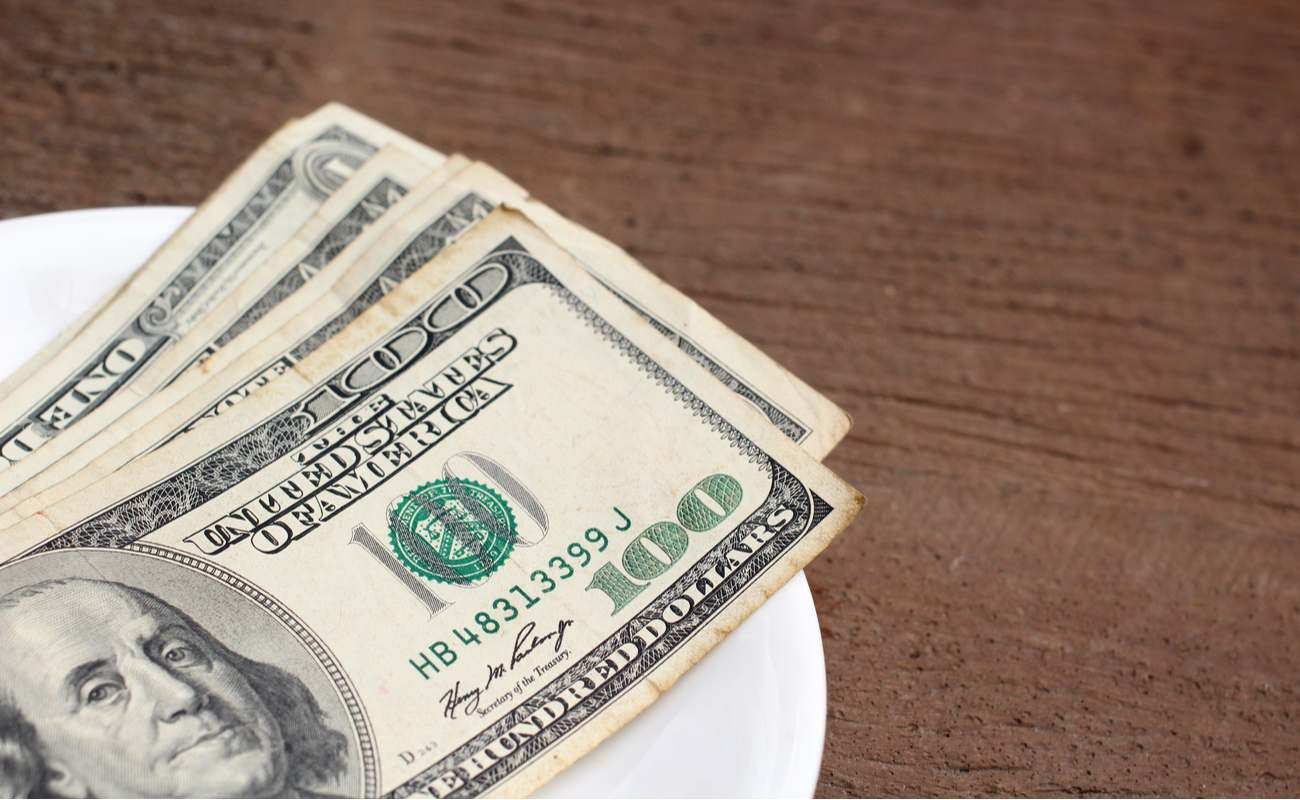 Dollar bills spread on plate as tip