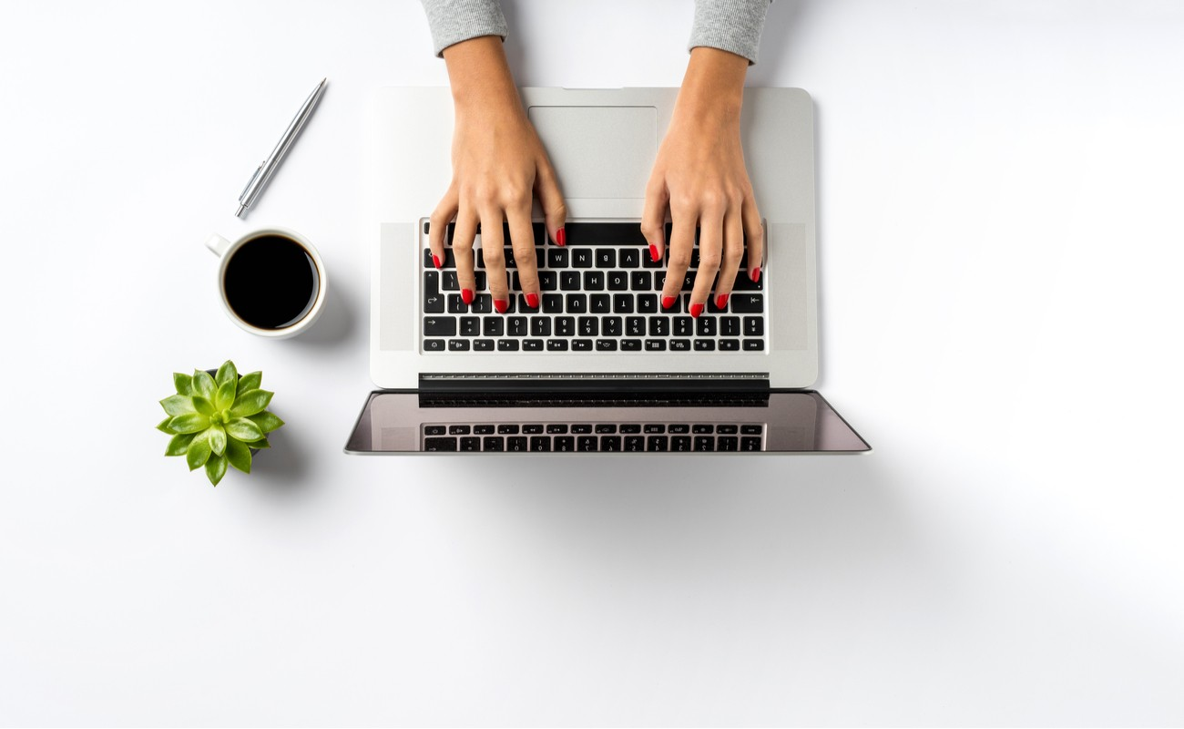 Female hands working on modern laptop, with coffee, a pen, and cactus next to the laptop