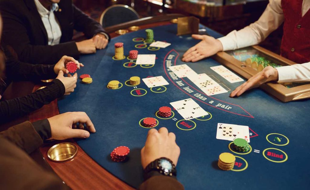 hands at the poker table with poker chips and cards