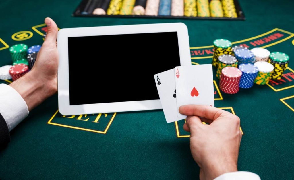 Hand holding cards and tablet device on blackjack table