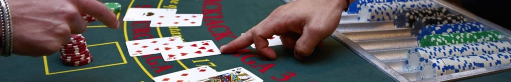 blackjack dealer and player pointing at card on blackjack table with chips
