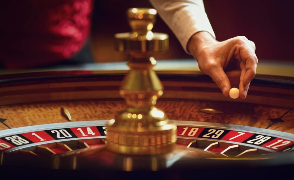 Croupier's hand placing a roulette ball on the wheel.