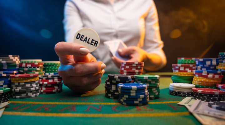 Casino dealer lifting dealer button surrounded by chips.
