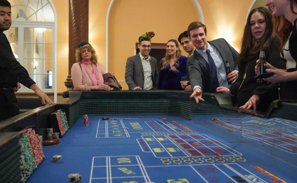 Man rolls and throws the dice during a game of craps, while people around the table watch