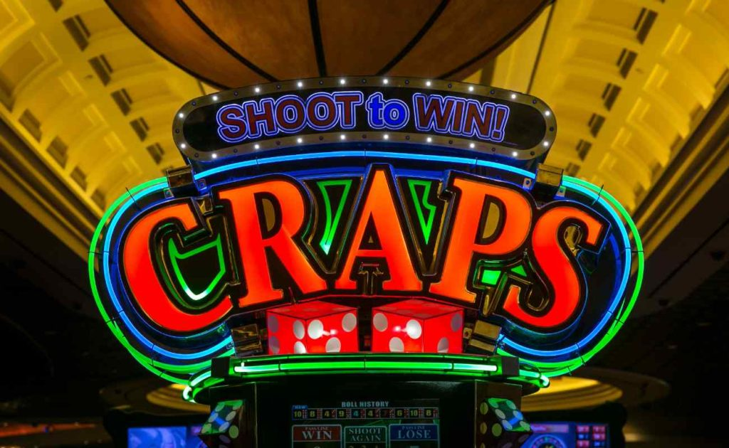 Neon-lit craps sign in casino saying Shoot to Win! above it