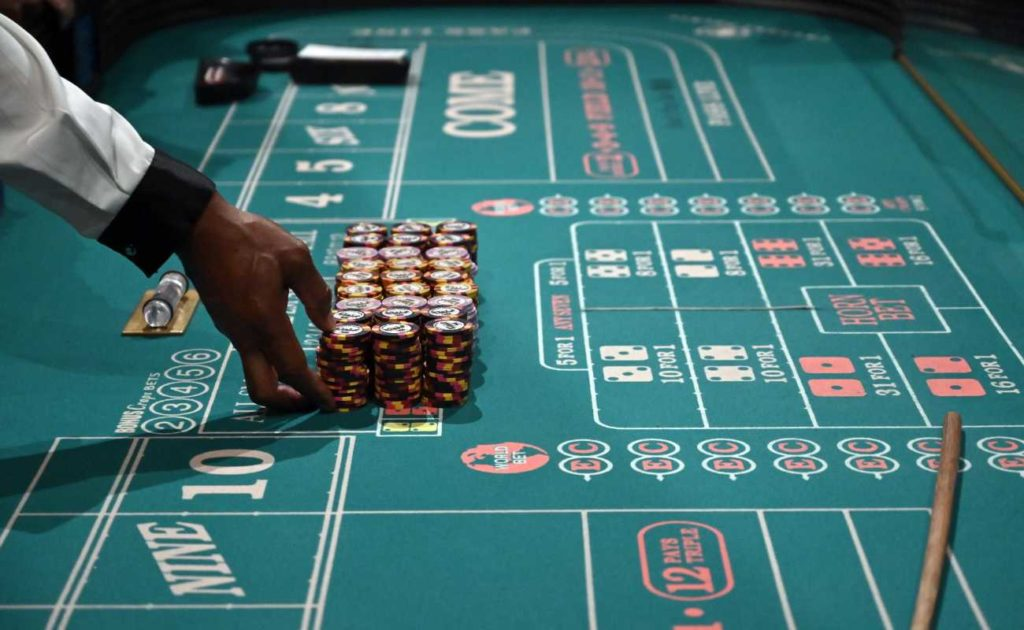 Close up of the hands of a craps dealer preparing stacks of casino chips