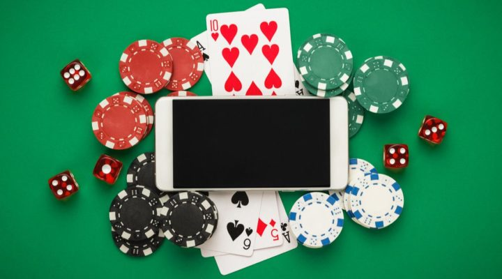 Mobile phone on casino table surrounded by chips and dice