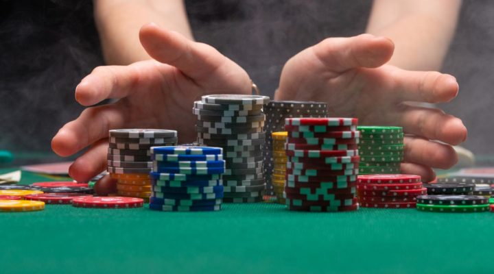 Close up of hands holding stacks of gambling chips